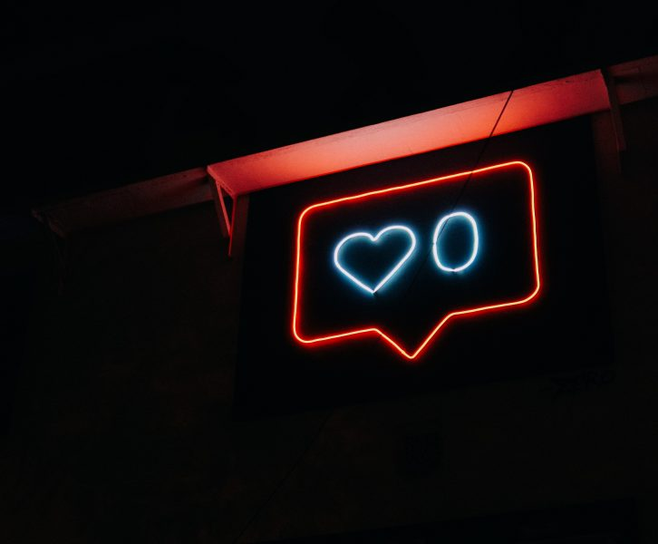 A neon sign showing zero likes on a social media post