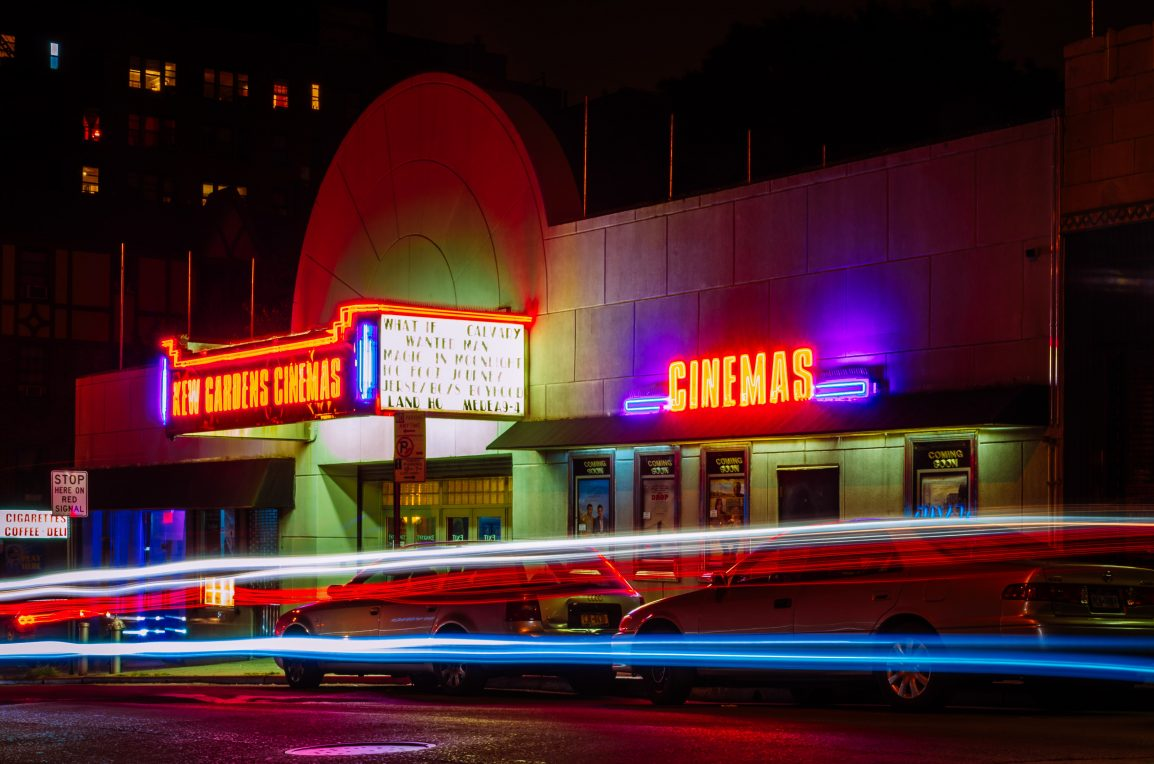 cars zoom by a cinema