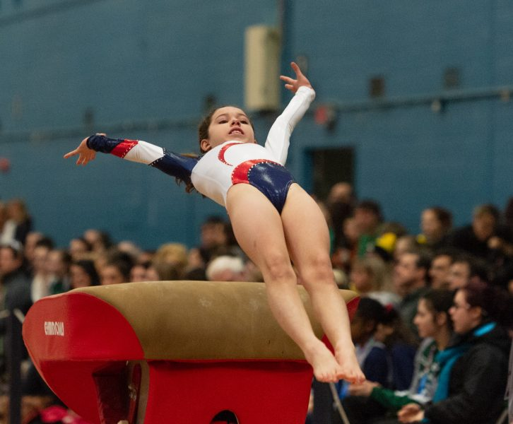 gymnast leaping over obstacle