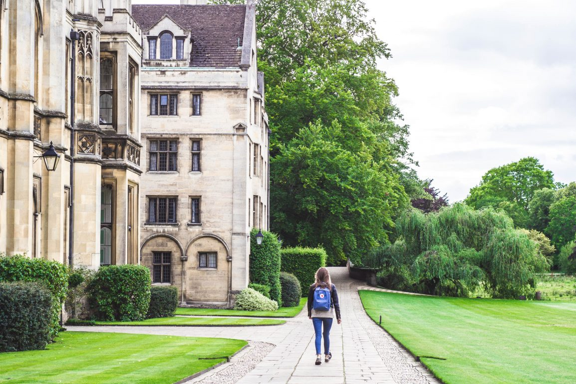 Girl walking through Cambridge campus with a backpack