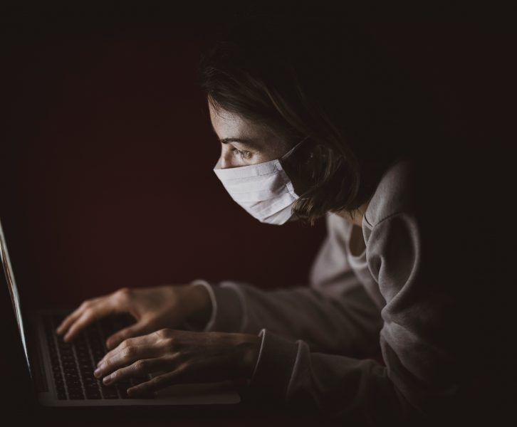 Person wearing mask and looking at a computer screen.
