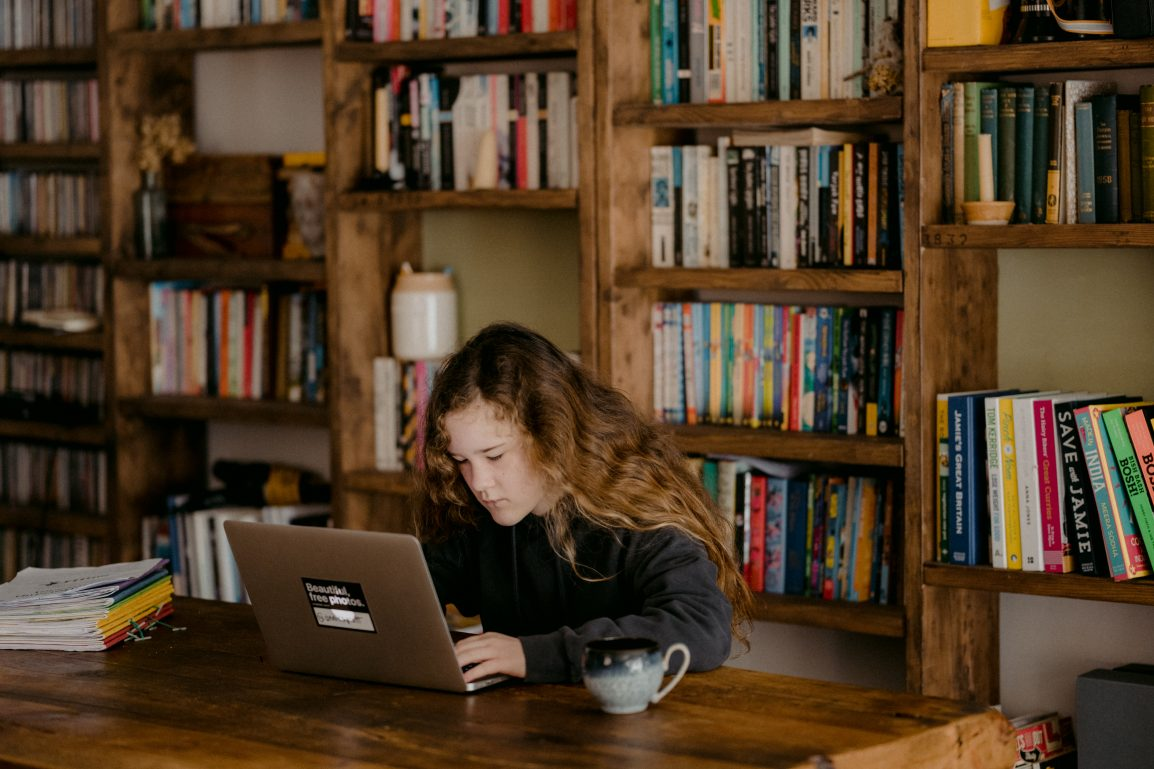 A girl looking at a computer in front of a bookshelf