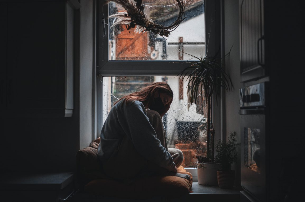 girl sitting in dark window wearing a mask